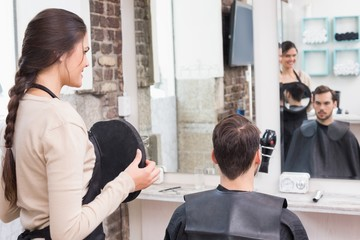 Pretty hair stylist showing man new haircut