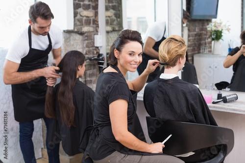 Leinwanddruck Bild Hairdressers working on their clients