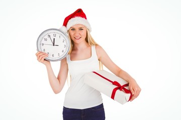 Festive blonde holding a clock and gift