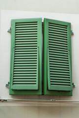 Finestre con persiane colore verde, facciata palazzo