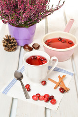 Cranberry tea in a cup on a wooden background