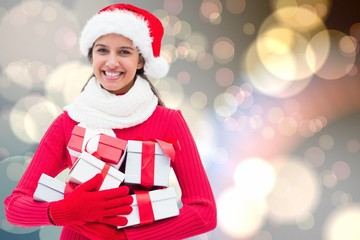 Composite image of festive brunette holding gifts
