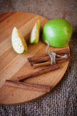 apples and cinnamon sticks on  wooden board, soft focus