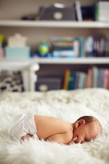 Cute little baby boy lying on bed
