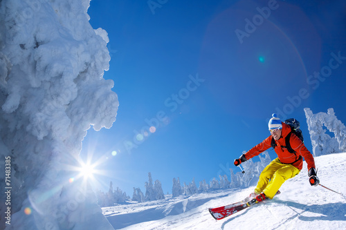 Skier against blue sky in high mountains - 71483385