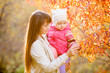 Young mother showing kid girl fallen leaves on tree