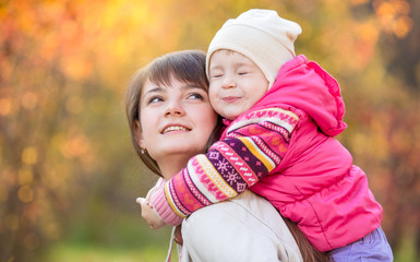 beautiful mother with kid girl outdoors over golden autumn backg