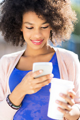 Afro woman with mobile phone and coffee