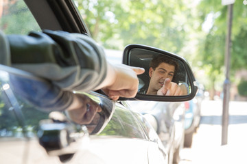 Reflection of Man Pointing in Side View Car Mirror