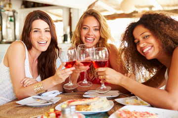 Group Of Female Friends Enjoying Meal In Outdoor Restaurant