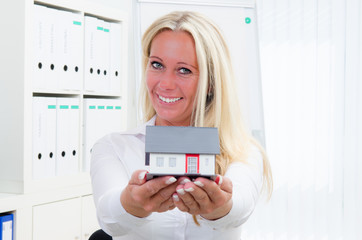 businessfrau zeigt miniaturhaus