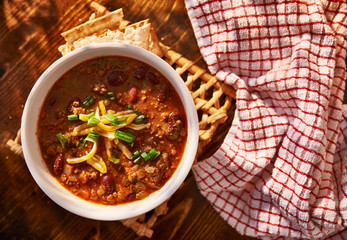 overhead photo of a bowl of chili with cheese and green onions