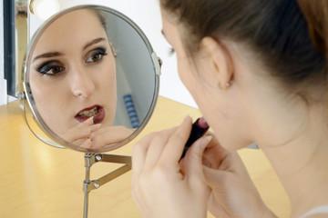 Twen beim Schminken mit Lippenstift