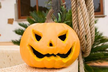 Halloween pumpkin in front of a well