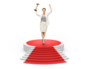 Businesswoman with gold cup on red carpet, isolated