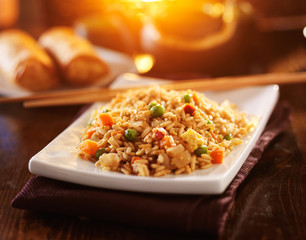 chinese vegetable fried rice on plate with orange glow