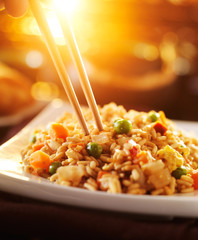 eating chinese vegetable fried rice with chopsticks
