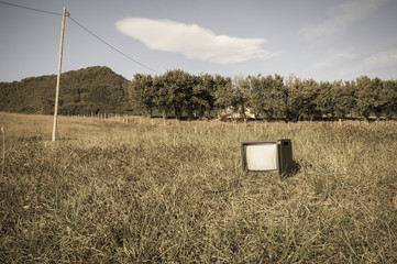 Abandoned old or antique tv in the grass field