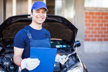 Mechanic holding a clipboard in front of a car