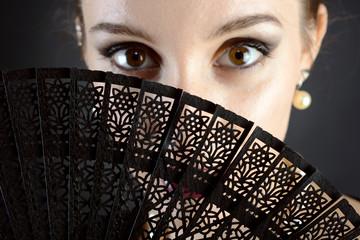 Frau schaut hinter schwarzem Fächer