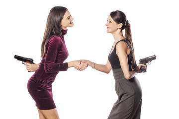 two young woman shake hands warmly with guns behind