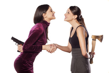 two young woman shake hands warmly with weapons behind