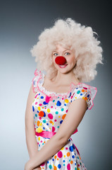 Clown with white wig against grey background