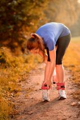 Frau legt ihre Gewichtsmanschetten zum Laufen an