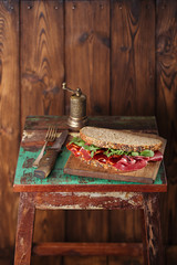 cured meat sandwich with seeded bread on old wooden table