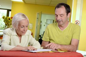 infirmier aidant une femme pour les démarches administratives