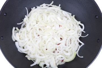 Onions overlying prepared meat in a cauldron