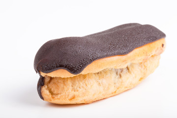 Cake eclair with chocolate on a light background. with dew