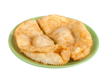 cheburek stuffed on a green plate isolated on white background