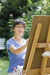 Frau malt ein Bild im Garten