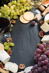 black background with cheeses, grapes, crackers and wine