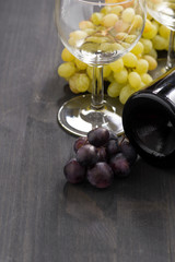 bottle of red wine, empty glass and grapes on wooden background