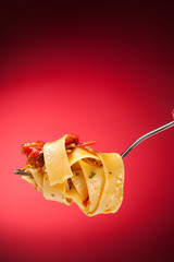 Tagliatelle with clams on a red background