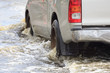 Car splashes through a large puddle on a flooded street - 71496732