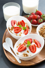 healthy breakfast - yogurt, fresh strawberries, granola and milk