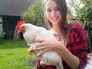 Young woman with a hen in her hands