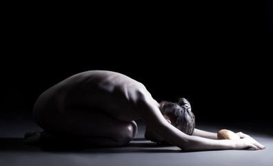 Image of skinny naked woman bowing before stone