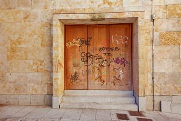 porte en fer rouillée sur façade de pierre avec graffitis