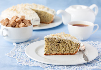 Delicious poppy seed cake with cup of tea on table close-up