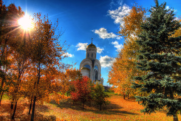 Church in the autumn forest on a background beautiful sky