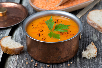 Spicy red lentil soup in a copper pot on a wooden table