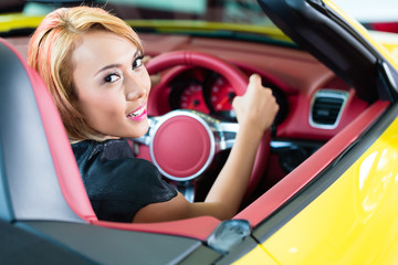 Asian woman testing new sports car