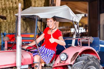 Bayrische Frau mit Dirndl fährt Trecker