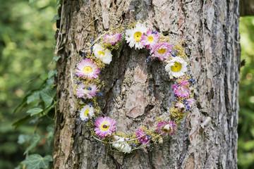 Blumenkranz hängt an einem Baum
