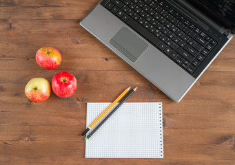 apples, laptop, notebook and pencils