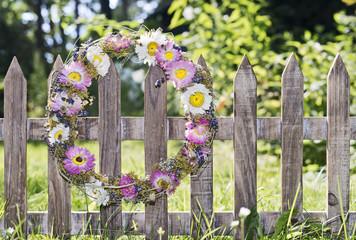 Blumenkranz hängt an einem Gartenzaun